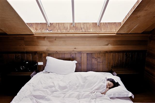 Asiatka na posteli v dřevem obloženém pokoji